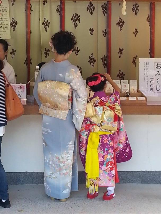 Magnifiquement vêtues, une mère et sa fille achètent des omikuji (voeux) au temple de Tenmangu