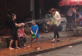 Les enfants se préparent à arroser les passants