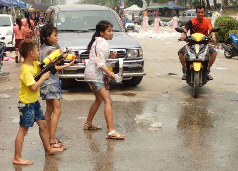 Des enfants flanqués au bord de la route se préparent à arroser les scooters, armés de pistolets à eau et de seaux